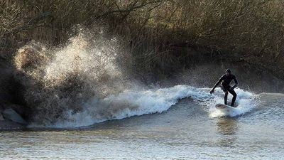 The extreme tide was welcomed by some adventurous surfers, but the tidal surge was not as high as the 14m expected.