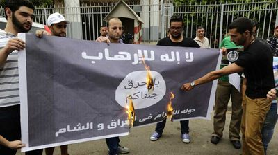 "At a more recent protest, a modified ISIS flag with the slogan ""We are coming to burn you"" was set alight."