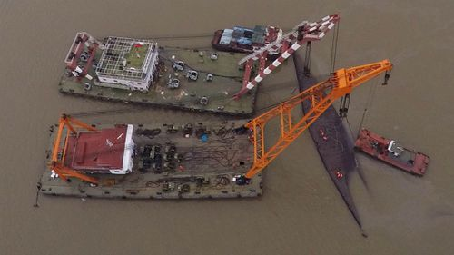 Battle to right capsized China ship as death toll hits 77