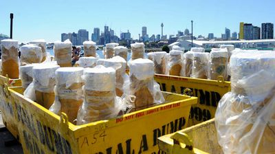 Rubbish skips filled with fireworks are loaded onto a barge in Sydney Harbour for the New Year's Eve show, which will include 11,000 shells, 25,000 shooting comets and over 100,000 individual effects. (AAP)