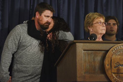 Ronald Johnson's children Toni and Jesse hug as their mother addresses the media.