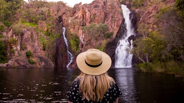 Woman standing in front of waterfall in the Northern Territory.