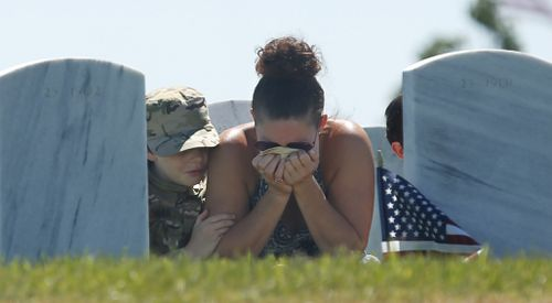 Heidi Hannah holds her head in her hands, as she is joined by her sons Tomas, 10, left, and Lucas, 8, right, at a Memorial Day visit to the grave of her oldest son, Army Specialist Taylor Hannah, at the Sacramento Valley National Cemetery in Dixon, California