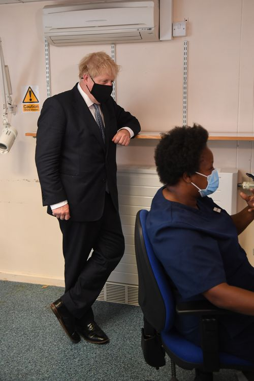 UK Prime Minister Boris Johnson wears a face mask as he visits Tollgate Medical Centre in Beckton
