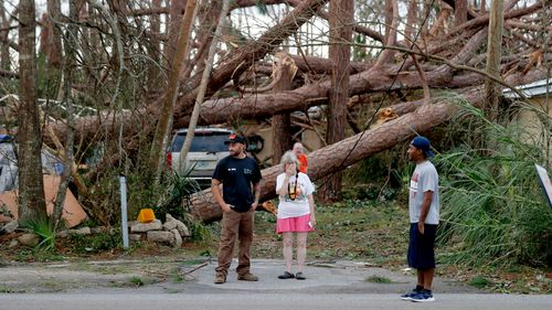 Joyce Fox stands in front of her heavily damaged home in the aftermath of Hurricane Michael in Panama City, Florida.