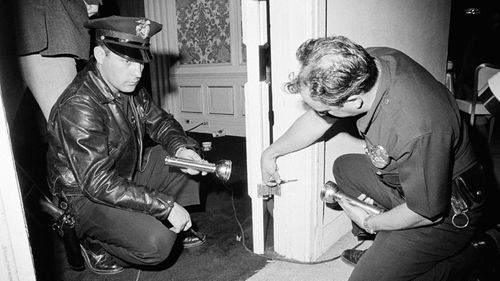 Police inspecting bullet holes in pantry Kennedy was fatally wounded inside. (AAP)