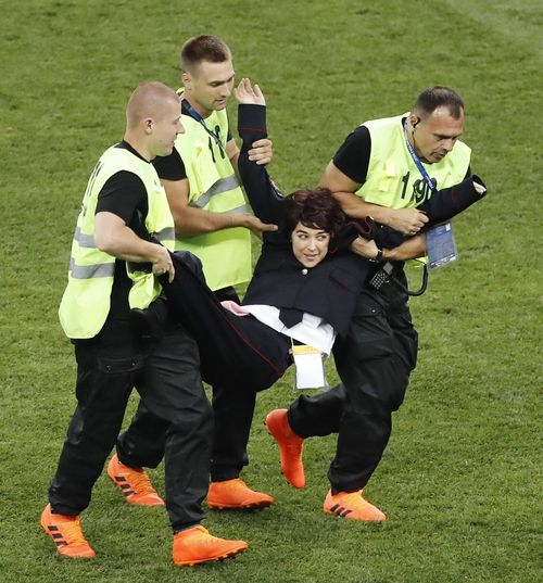 A woman who invaded the pitch is carried out by security guards during the World Cup final between France and Croatia at Luzhniki Stadium in Moscow on July 15, 2018. Russian protest group and musical act Pussy Riot has claimed responsibility for the incident. (Kyodo via AP Images)
