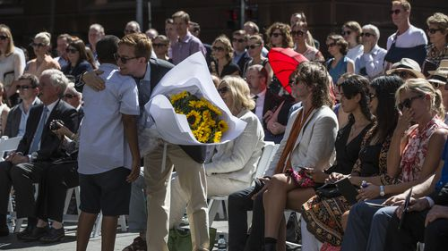Local school student Jack Tighe hugged Mr Johnson's partner, Thomas  Zinn, after presenting the bouquet of sunflowers. (AAP)