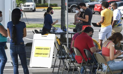 People register to receive a COVID-19 vaccine shot at a mobile vaccination site in Orlando, Florida.