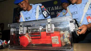 Indonesian Air Force military police officers place the flight data recorder in a savety box. (AAP)