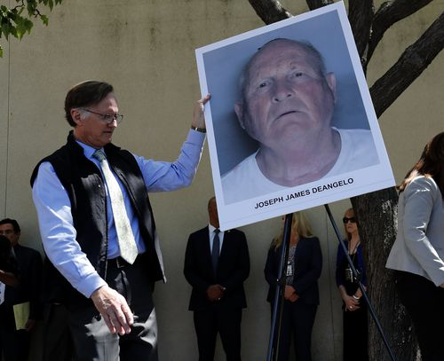7 An official puts a mug shot on an easel stand, of the suspect identified as Joseph James DeAngelo. (AAP)
