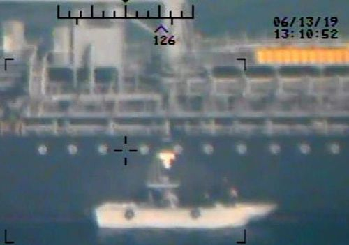 Photo taken from a US Navy helicopter showing what the Navy says are members of the Islamic Revolutionary Guard Corps Navy removing an unexploded limpet mine from the M/T Kokuka Courageous.