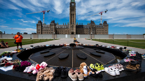 Shoes line the edge of the Centennial Flame on Parliament Hill in memory of the 215 children whose remains were found at the grounds of the former Kamloops Indian Residential School.