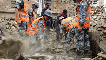 Rescue workers take part in the rescue operation where several houses have collapsed at Vhaktapur district. (AAP)