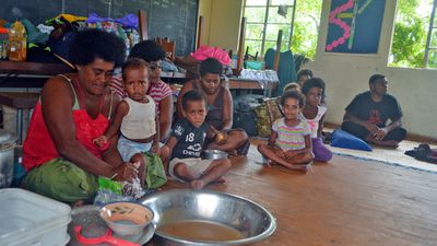 Families from Wainiveidilo settlement prepare their lunch at a school used as an evacuation centre in Navua, Fiji. (AP)