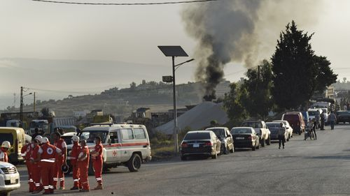 Lebanese Red Cross volunteers gather at a street next to the scene where a fuel tanker exploded in Tleil village.