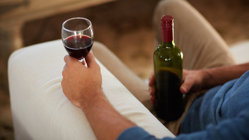 Man drinking red wine and holding a bottle