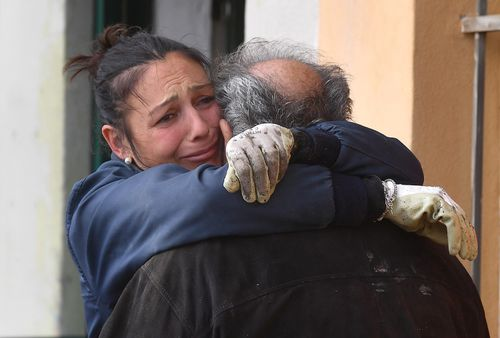 A woman hugs her father as they try to save their household goods after the strong storm in Boccadasse, Genova.