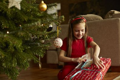 Child unwrapping Christmas gift
