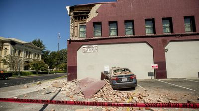Bricks rest atop a car in Napa, Calif., from a damaged wall following an earthquake Sunday, Aug. 24, 2014. (AAP)
