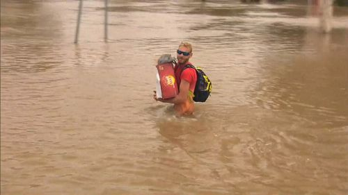 A man walks through floodwaters with a beer carton. (9NEWS)