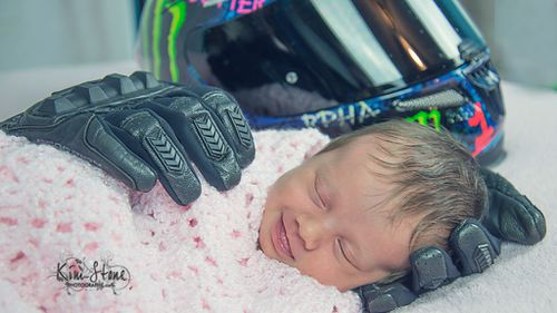 Touching photograph of baby cradled in late father's motorcycle gloves goes viral