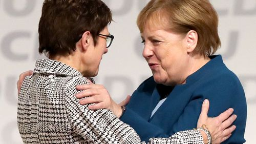 German Chancellor Angela Merkel embraces her newly-elected replacement as CDU leader, Annegret Kramp-Karrenbauer.