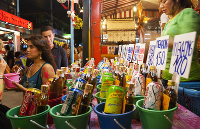 Haad Rin, Ko Phangan, Thailand - August 29, 2007: A Thai woman sells buckets of soft drinks and liquor to visitors celebrating the monthly Full Moon Party in Haad Rin, a beach destination on the island of Ko Phangan, Thailand