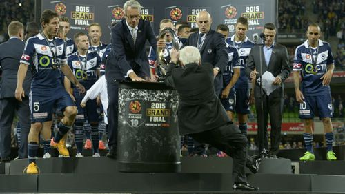 FFA CEO David Gallop and the Melbourne Victory look on in shock as Frank Lowy begins his fall. (AAP)