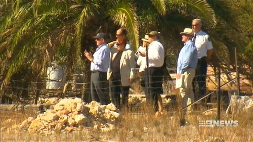 The deputy coroner and counsel assisting at the property. (9NEWS)
