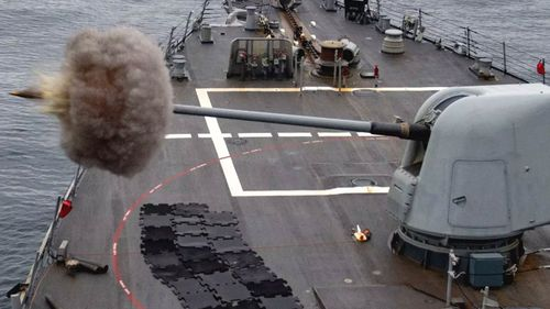 A US Navy vessel fires a shell from its five-inch deck gun.