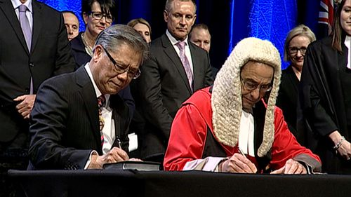 Hieu Van Le signs documents at his swearing in as South Australia's new governor. Picture: 9NEWS