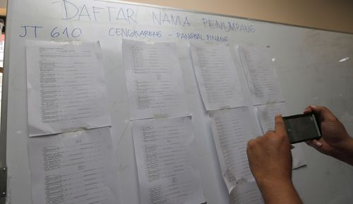 A man takes photo of the list of passengers of Lion Air flight JT610 at Soekarno-Hatta International Airport in Tangerang.