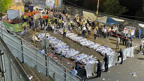 Israeli security officials and rescuers stand around the bodies of victims who died during a Lag Ba'Omer celebrations at Mt Meron in northern Israel.
