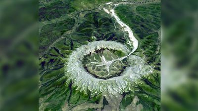 """This is neither an impact crater nor a volcano. It is a perfect circular intrusion, about 10 km in diameter with a topographic ridge up to 600 m high. The Kondyor Massif is located in Eastern Siberia, Russia, north of the city of Khabarovsk. It is a rare form of igneous intrusion called alkaline-ultrabasic massif and it is full of rare minerals."" (NASA/METI/AIST/Japan Space Systems, and U.S./Japan ASTER Science Team)"