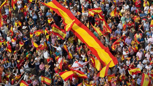 Thousands of pro-Spanish unity supporters donning Spanish flags have rallied in a central Madrid plaza to protest the Catalan regional government's drive to separate from Spain. (AP)