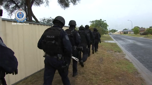 Tactical police prepare to execute a search warrant shortly after 7am yesterday.