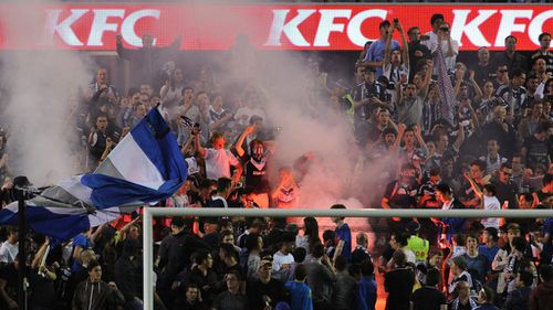 Fans light a flare during the round seven A-League match between the Melbourne Victory and Brisbane Roar at Etihad Stadium. (Getty)