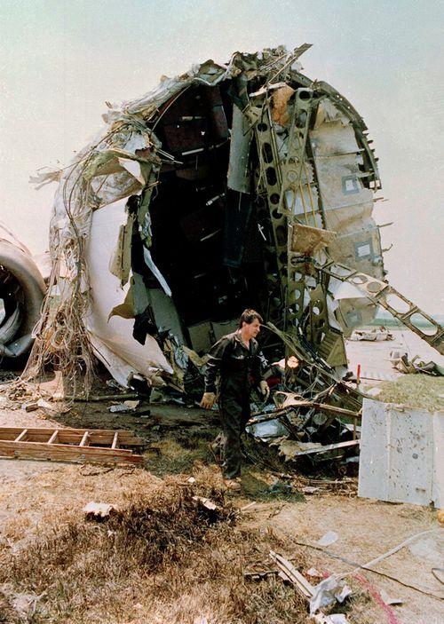 A National Transportation Safety Board investigator walks in front of the torn portion of the passenger compartment of the United Airlines DC-10 that crashed and exploded on landing at Sioux Gateway Airport, near Sioux City, Iowa