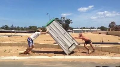 Troublesome tradies in Perth have filmed themselves tormenting a mate by locking him in the portaloo he was using before toppling it on its side.