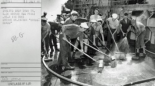 Sailors wash down the highly contaminated deck of the captured German battleship USS Prinz Eugene (IX 300) after the Baker explosion. The ship was so radioactive that it was later sunk. (National Security Archive)
