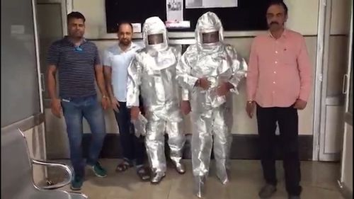 Photos and a video of the father and son, dressed in silver space suits, being escorted by officials have gone viral.
