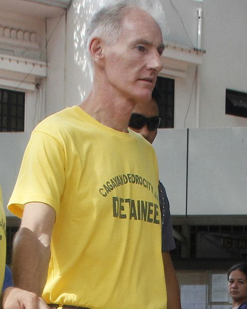 Australian Peter Gerald Scully in handcuffs as he arrives at Cagayan de Oro city hall in southern Philippines. Scully and his Filipino girlfriend Carme Ann Alvarez were charged with raping and trafficking two girls aged 9 and 12 in a southern Philippine city. Scully is also under investigation in the death of a girl whose remains were found inside his house in another southern province. (AAP)