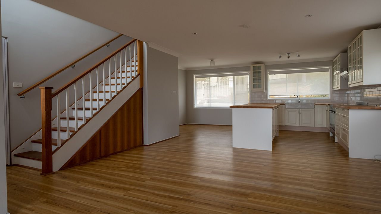 BEFORE: The living space and kitchen with polished timber floors