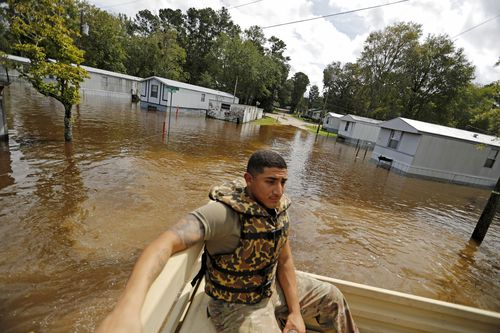 U.S. Army Spc. Daniel Ochoa rides in the back of a high water vehicle while searching for residents to evacuate from a flooded neighborhood in Spring Lake.