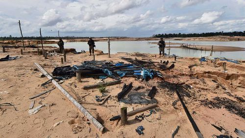 Peruvian police officers stand guard in a recovered area, deforested by illegal gold mining in the Madre de Dios province.