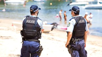Police at Clareville Beach in northern Sydney ensure crowd limits fall within guidelines for coronavirus restrictions in the city.