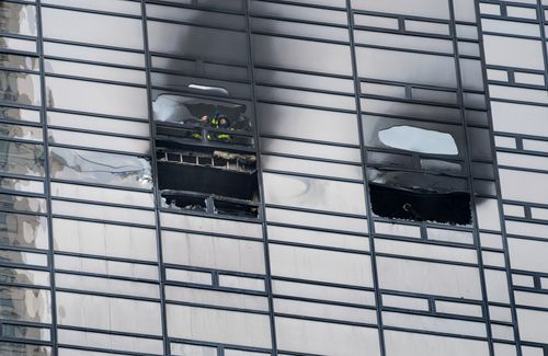 Firefighters look out from the window of a fire damaged apartment in Trump Tower in New York on Saturday, April 7, 2018. (AAP)