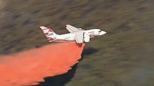 Fixed-wing aircraft are dispersing fire retardant over the blaze.