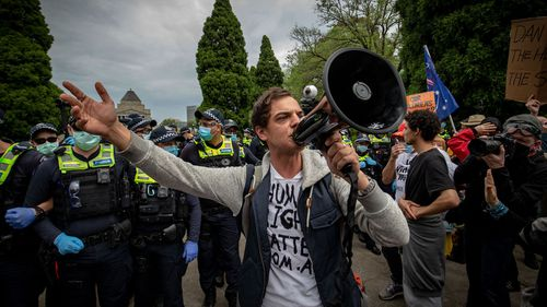 A protester speaks with a megaphone on October 23, 2020 in Melbourne, Australia